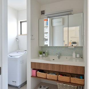 Immagine di un bagno di servizio nordico con piastrelle verdi, piastrelle di vetro, pareti bianche, lavabo integrato, top in superficie solida e pavimento beige