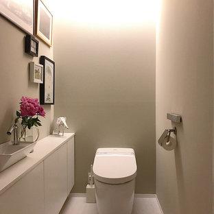 東京23区のモダンスタイルのおしゃれなトイレ・洗面所 (フラットパネル扉のキャビネット、白いキャビネット、グレーの壁、ベッセル式洗面器、白い床、白い洗面カウンター) の写真