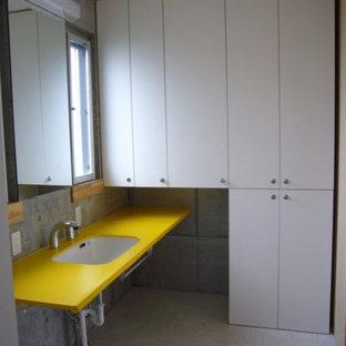 Immagine di un bagno di servizio moderno con ante a filo, ante bianche, pareti grigie, pavimento in linoleum, lavabo sottopiano, top in laminato e pavimento beige