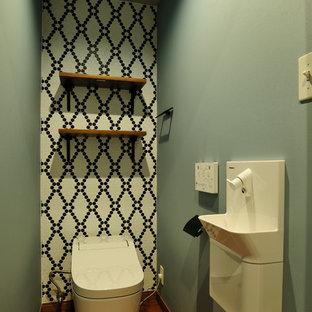 東京都下のアジアンスタイルのおしゃれなトイレ・洗面所 (壁付け型シンク、茶色い床、モノトーンのタイル、緑の壁、濃色無垢フローリング) の写真