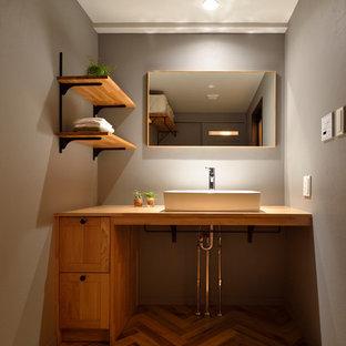 他の地域のインダストリアルスタイルのおしゃれなトイレ・洗面所 (落し込みパネル扉のキャビネット、中間色木目調キャビネット、グレーの壁、無垢フローリング、ベッセル式洗面器、木製洗面台、茶色い床、ブラウンの洗面カウンター) の写真