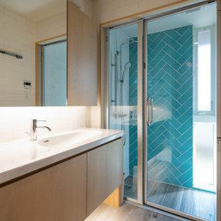 Bild på ett funkis blå blått badrum, med släta luckor, skåp i ljust trä, vit kakel, porslinskakel, vita väggar, ett integrerad handfat, bänkskiva i kvarts och grått golv