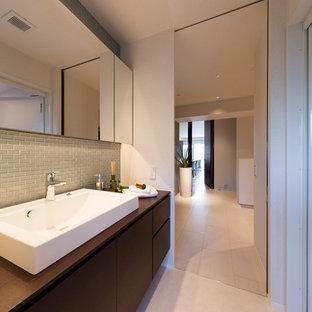 Esempio di un bagno di servizio minimal con ante in legno bruno, piastrelle grigie, pareti bianche, lavabo a bacinella, top in legno, pavimento beige e top marrone