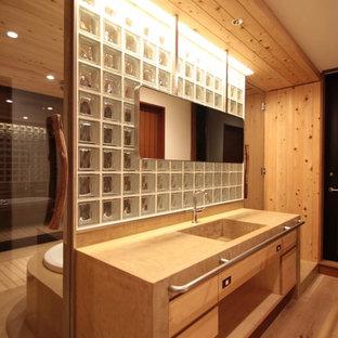 東京23区のコンテンポラリースタイルのおしゃれなトイレ・洗面所 (フラットパネル扉のキャビネット、茶色いキャビネット、茶色い壁、無垢フローリング、一体型シンク、茶色い床、ブラウンの洗面カウンター) の写真