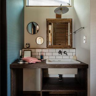 他の地域の中くらいのインダストリアルスタイルのおしゃれなトイレ・洗面所 (オープンシェルフ、白いタイル、サブウェイタイル、白い壁、一体型シンク、ラミネートカウンター、ブラウンの洗面カウンター) の写真