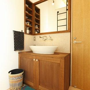 他の地域の小さいカントリー風おしゃれなトイレ・洗面所 (落し込みパネル扉のキャビネット、ヴィンテージ仕上げキャビネット、白い壁、淡色無垢フローリング、ベッセル式洗面器、木製洗面台、ベージュの床、ブラウンの洗面カウンター) の写真
