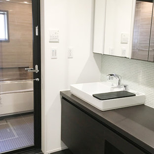 Стильный дизайн: большой туалет в современном стиле с фасадами с декоративным кантом, стеклянной плиткой, накладной раковиной, черным полом и черной столешницей - последний тренд