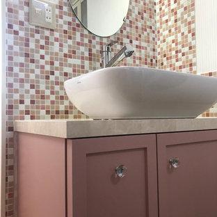 Réalisation d'un petit WC et toilettes chalet avec un placard à porte affleurante, des portes de placard rouges, un carrelage rose, carrelage en mosaïque, un mur rose, un sol en linoléum, un lavabo posé, un plan de toilette en bois, un sol beige, un plan de toilette rose, meuble-lavabo encastré, un plafond en papier peint et du papier peint.