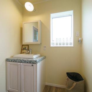 他の地域のビーチスタイルのおしゃれなトイレ・洗面所 (レイズドパネル扉のキャビネット、黄色い壁、濃色無垢フローリング、オーバーカウンターシンク、タイルの洗面台、茶色い床) の写真