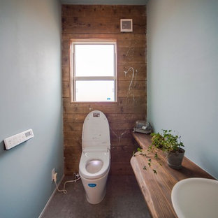 На фото: большие туалеты в морском стиле с открытыми фасадами, коричневыми фасадами, белыми стенами, полом из винила, монолитной раковиной, столешницей из дерева, серым полом и коричневой столешницей