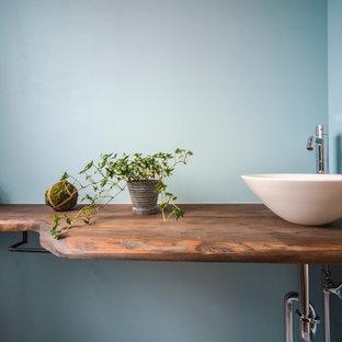 Стильный дизайн: большой туалет в морском стиле с открытыми фасадами, коричневыми фасадами, синими стенами, полом из винила, монолитной раковиной, столешницей из дерева и серым полом - последний тренд