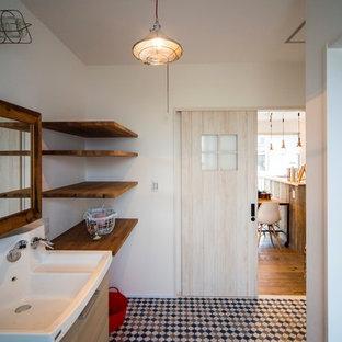 他の地域の広いビーチスタイルのおしゃれなトイレ・洗面所 (オープンシェルフ、茶色いキャビネット、スレートタイル、白い壁、クッションフロア、一体型シンク、木製洗面台、青い床) の写真