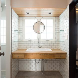 他の地域の中くらいのコンテンポラリースタイルのおしゃれなトイレ・洗面所 (フラットパネル扉のキャビネット、中間色木目調キャビネット、白い壁、コンクリートの床、オーバーカウンターシンク、グレーの床) の写真