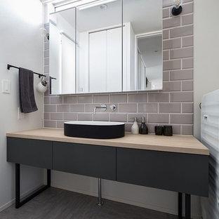 Exemple d'un WC et toilettes industriel avec un placard à porte plane, des portes de placard noires, un mur blanc, béton au sol, une vasque, un plan de toilette en bois et un sol gris.