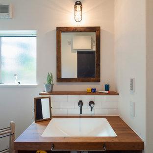 他の地域の中くらいのビーチスタイルのおしゃれなトイレ・洗面所 (オープンシェルフ、淡色木目調キャビネット、白いタイル、サブウェイタイル、白い壁、セメントタイルの床、亜鉛の洗面台、グレーの床、白い洗面カウンター) の写真