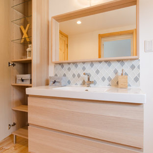 Inspiration for a medium sized scandinavian cloakroom in Other with flat-panel cabinets, light wood cabinets, multi-coloured tiles, glass tiles, white walls, light hardwood flooring, an integrated sink, solid surface worktops, beige floors and white worktops.
