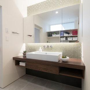 他の地域の中くらいのモダンスタイルのおしゃれなトイレ・洗面所 (オープンシェルフ、茶色いキャビネット、ベージュのタイル、ガラスタイル、白い壁、オーバーカウンターシンク、人工大理石カウンター、グレーの床、ブラウンの洗面カウンター) の写真