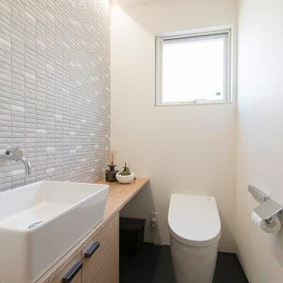 Cette image montre un WC et toilettes minimaliste de taille moyenne avec des portes de placard marrons, un WC à poser, un carrelage gris, un mur blanc, un sol noir, un placard à porte affleurante, des carreaux de porcelaine, un lavabo posé, meuble-lavabo encastré, un plafond en papier peint et du papier peint.