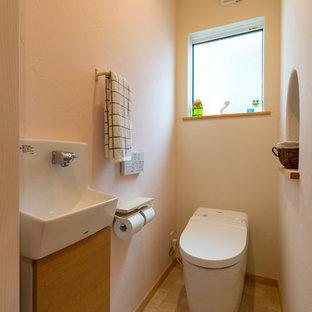 他の地域の地中海スタイルのおしゃれなトイレ・洗面所 (フラットパネル扉のキャビネット、中間色木目調キャビネット、白い壁、ペデスタルシンク、ベージュの床) の写真