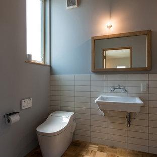 На фото: туалеты в морском стиле с унитазом-моноблоком, белой плиткой, паркетным полом среднего тона и подвесной раковиной