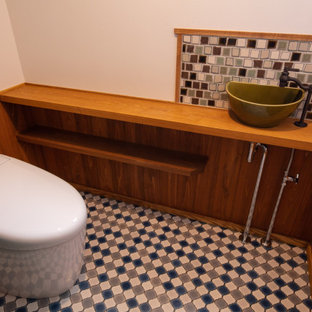 Inspiration for a farmhouse cloakroom in Other with open cabinets, green cabinets, a one-piece toilet, multi-coloured tiles, mosaic tiles, white walls, vinyl flooring, a built-in sink, wooden worktops, multi-coloured floors, brown worktops, a built in vanity unit, a wallpapered ceiling and wallpapered walls.
