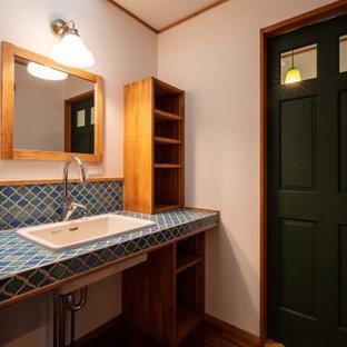 Идея дизайна: туалет в стиле кантри с бирюзовыми фасадами, разноцветной плиткой, плиткой мозаикой, белыми стенами, темным паркетным полом, врезной раковиной, столешницей из плитки, коричневым полом, бирюзовой столешницей, встроенной тумбой, потолком с обоями и обоями на стенах