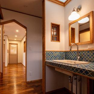 На фото: туалет в стиле кантри с открытыми фасадами, бирюзовыми фасадами, разноцветной плиткой, плиткой мозаикой, белыми стенами, темным паркетным полом, настольной раковиной, столешницей из плитки, коричневым полом, бирюзовой столешницей, встроенной тумбой, потолком с обоями и обоями на стенах