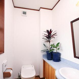 Mid-Century Gästetoilette mit hellbraunen Holzschränken, weißer Wandfarbe, braunem Holzboden, Einbauwaschbecken, gefliestem Waschtisch und braunem Boden in Sonstige