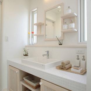 他の地域の広いモダンスタイルのおしゃれなトイレ・洗面所 (インセット扉のキャビネット、白いキャビネット、白いタイル、セラミックタイル、白い壁、リノリウムの床、ベッセル式洗面器、タイルの洗面台、ベージュの床、白い洗面カウンター、造り付け洗面台、クロスの天井、壁紙) の写真