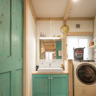 他の地域の地中海スタイルのおしゃれなトイレ・洗面所 (落し込みパネル扉のキャビネット、青いキャビネット、白い壁、無垢フローリング、ベッセル式洗面器、木製洗面台、マルチカラーの床、ベージュのカウンター) の写真