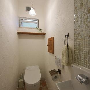 他の地域, のカントリー風おしゃれなトイレ・洗面所 (一体型トイレ、白い壁、磁器タイルの床、マルチカラーの床) の写真