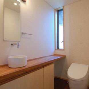 Exemple d'un WC et toilettes asiatique avec des portes de placard beiges, un carrelage blanc, un mur blanc, un sol en carrelage de céramique, un plan de toilette en bois, un sol marron, une vasque et un plan de toilette marron.