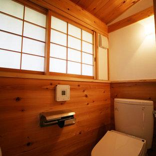 Ejemplo de aseo de estilo zen, pequeño, con sanitario de pared, paredes blancas, suelo de madera en tonos medios y suelo marrón