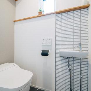 Nordische Gästetoilette mit weißen Fliesen, Porzellanfliesen, Kiesel-Bodenfliesen, schwarzem Boden, weißer Wandfarbe und Waschtischkonsole in Sonstige