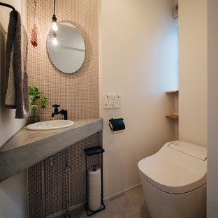 Esempio di un bagno di servizio nordico con piastrelle bianche, piastrelle in gres porcellanato, pareti bianche, pavimento in cemento, lavabo da incasso e pavimento grigio
