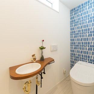 Идея дизайна: туалет в стиле кантри с синей плиткой, полом из винила, белым полом и коричневой столешницей