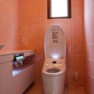 На фото: туалет в стиле модернизм с розовой плиткой, керамической плиткой и розовым полом с