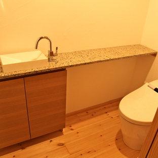 На фото: туалеты в стиле модернизм с фасадами с декоративным кантом, бежевыми фасадами, унитазом-моноблоком, белыми стенами, светлым паркетным полом, накладной раковиной, столешницей из цинка и бежевым полом