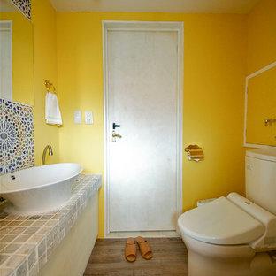 Esempio di un bagno di servizio mediterraneo con piastrelle grigie, piastrelle multicolore, pareti gialle, pavimento in legno massello medio, lavabo a bacinella, top piastrellato e WC a due pezzi