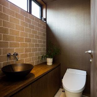 他の地域のミッドセンチュリースタイルのおしゃれなトイレ・洗面所 (フラットパネル扉のキャビネット、濃色木目調キャビネット、グレーの壁、木製洗面台、ベージュの床、ブラウンの洗面カウンター) の写真