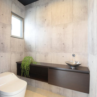 Photo of a modern cloakroom in Other with dark wood cabinets, grey walls, a vessel sink and yellow floors.