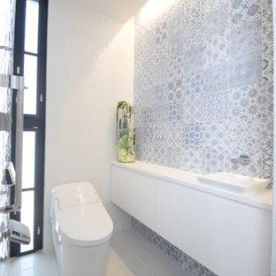 他の地域のモダンスタイルのおしゃれなトイレ・洗面所 (白いキャビネット、青いタイル、磁器タイル、白い壁、磁器タイルの床、白い床) の写真