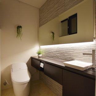 Idée de décoration pour un WC et toilettes minimaliste avec des portes de placard en bois sombre, un carrelage gris, des carreaux de porcelaine, un sol en vinyl et un sol jaune.