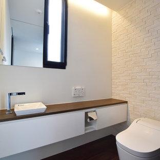 他の地域のモダンスタイルのトイレ・洗面所の画像 (フラットパネル扉のキャビネット、白いキャビネット、白い壁、オーバーカウンターシンク、茶色い床)