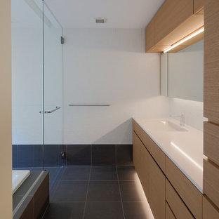 Foto di un bagno di servizio minimal con ante lisce, ante marroni, pareti bianche, lavabo integrato e pavimento nero