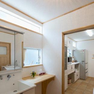 Modelo de aseo de estilo zen con puertas de armario blancas, sanitario de una pieza, paredes blancas, suelo de baldosas de terracota, suelo naranja y encimeras blancas