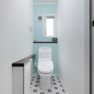 Пример оригинального дизайна: туалет в восточном стиле с плоскими фасадами, белыми фасадами, синими стенами, разноцветным полом, унитазом-моноблоком и полом из винила