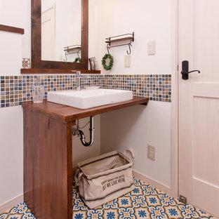 Diseño de aseo campestre con paredes blancas, lavabo sobreencimera, armarios abiertos, baldosas y/o azulejos multicolor, baldosas y/o azulejos en mosaico, suelo vinílico, encimera de madera y suelo multicolor