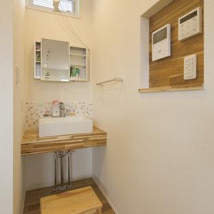 Modern inredning av ett mellanstort brun brunt toalett, med öppna hyllor, vita skåp, flerfärgad kakel, keramikplattor, vita väggar, målat trägolv, ett nedsänkt handfat och grått golv