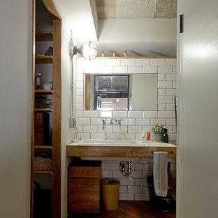 Immagine di un bagno di servizio industriale con piastrelle bianche, pareti bianche, pavimento in legno massello medio, lavabo sottopiano, top piastrellato e pavimento beige